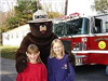 Smokey Bear with children in front of the firetruck