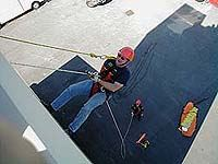 Fire Rescue Member scaling a wall with a rope